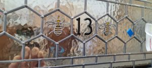 Stained Glass with a bee and the number 13 above a Accoya Door